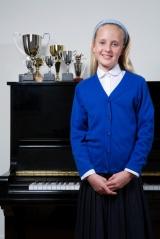 Girl standing beside a piano